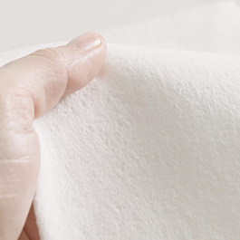 A closeup of a white paper towel with a hand gripping it