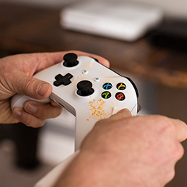 Two hands grip a white Xbox controller with an orange food smudge near the buttons on the right side