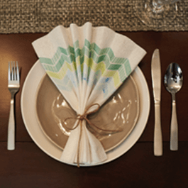 A table setting shown from above including a white plate, silver cutlery, and a brown folded napkin on top of a wooden table