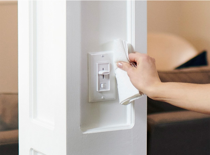 Person cleaning off light switch with Viva Paper Towels