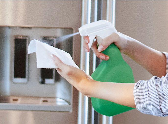 Person spraying cleaning on to Viva Paper Towels to clean home